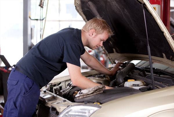 car mechanic looking under hood of car